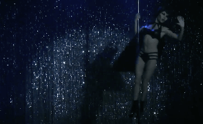 video image of woman performing maleficent pole dance routine on stage with cape and headpiece, pole dancing