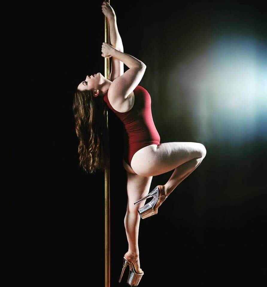 woman in maroon on pole doing shoulder mount in heels for photoshoot, pole fitness, pole dancing