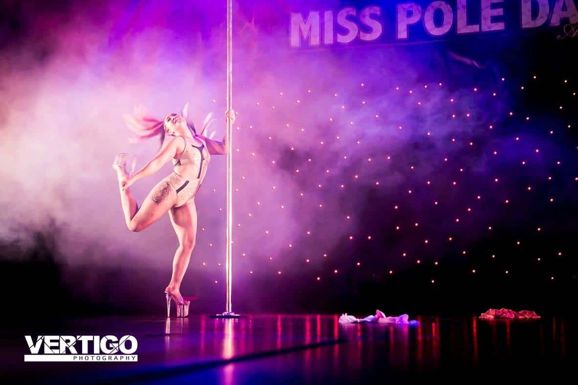 Woman performing on stage with pole kick hair flick eight inch heels Miss pole dance victoria, pole fitness