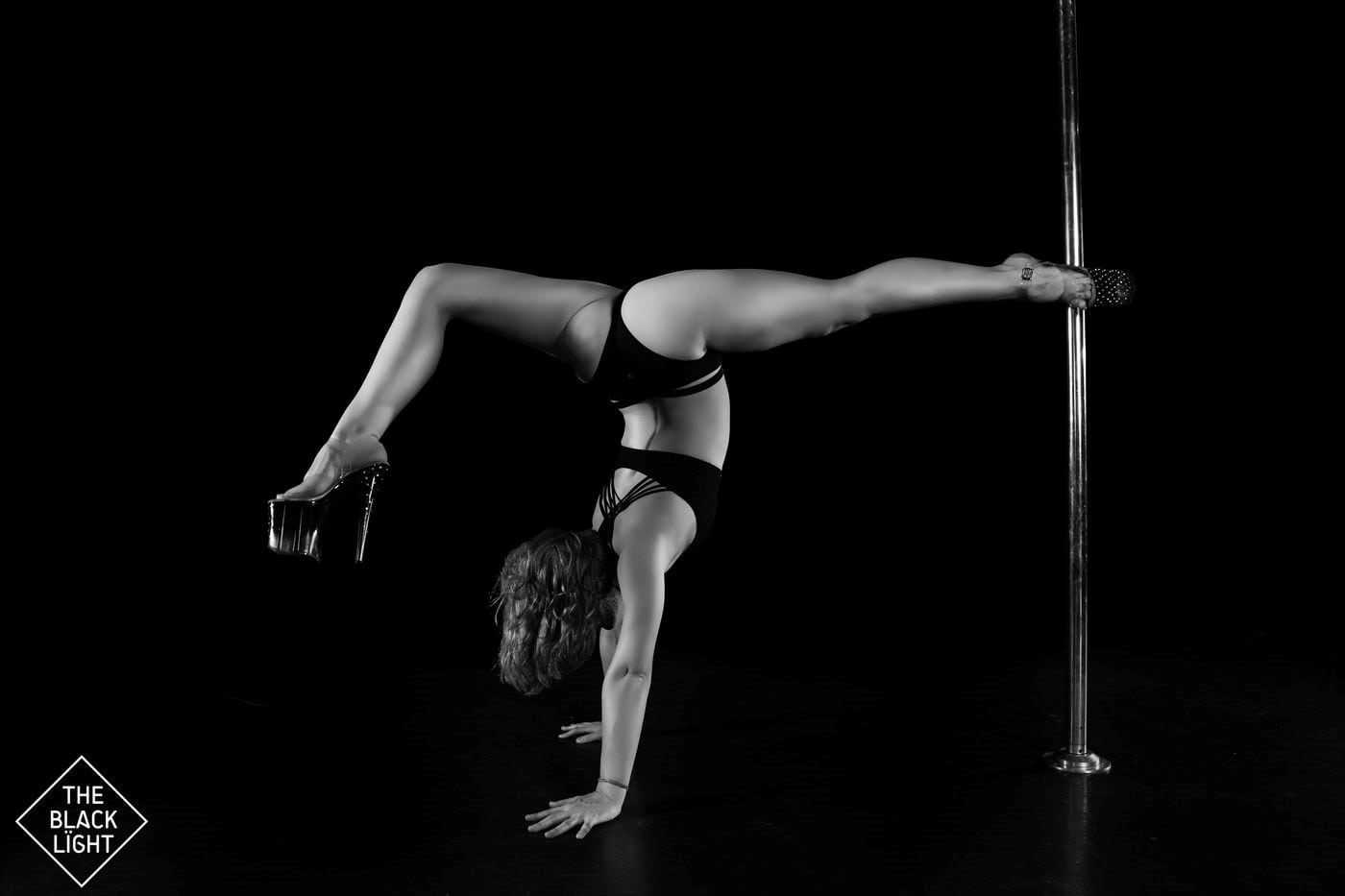 black and white image of woman doing split against pole for photoshoot