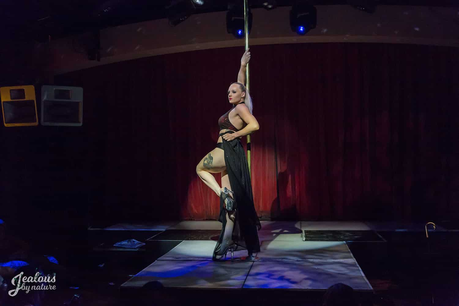 Woman performing in pole competition black flowy skirt high heels, pole fitness, pole dancing
